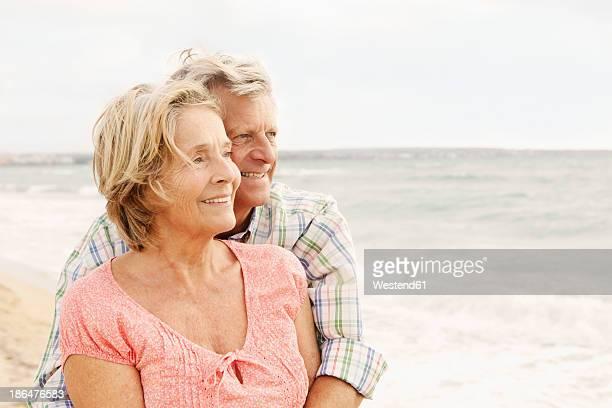 Spain, Senior couple embracing on beach at Palma de Mallorca