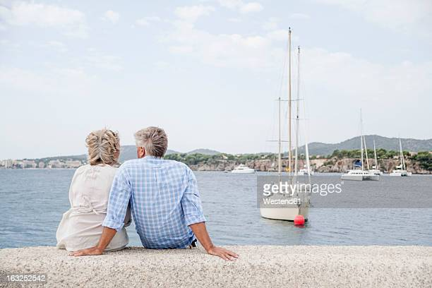 Spain, Senior couple sitting at harbour