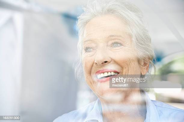 Spain, Senior woman looking through window, smiling