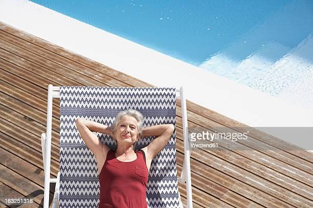 Spain, Senior woman relaxing on deck chair at beach