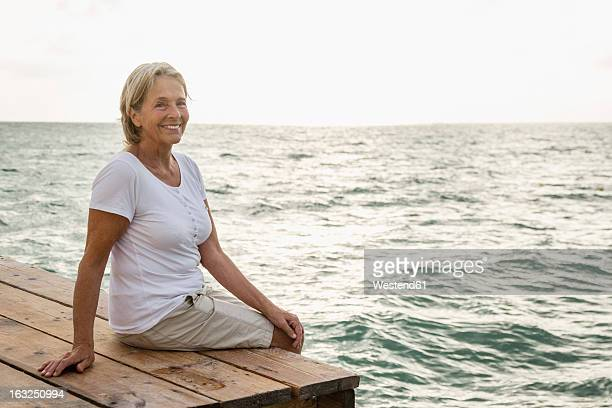 Spain, Senior woman sitting on jetty at the sea