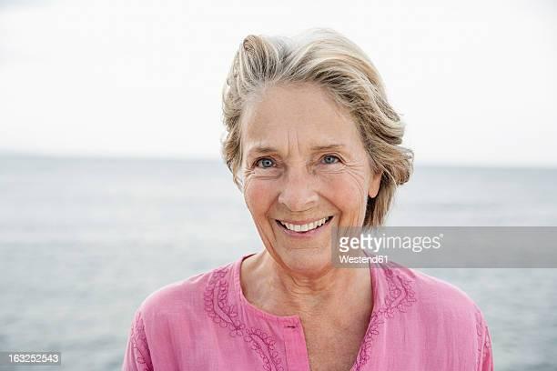 spain, senior woman smiling at atlantic ocean - 65 69 ans photos et images de collection