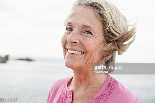 spain, senior woman smiling at atlantic ocean - alleen één seniore vrouw stockfoto's en -beelden