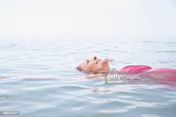Spain, Senior woman swimming in Atlantic
