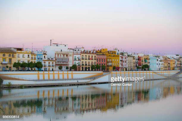 spain, seville, colorful residential building reflecting in guadalquivir river - seville stock pictures, royalty-free photos & images