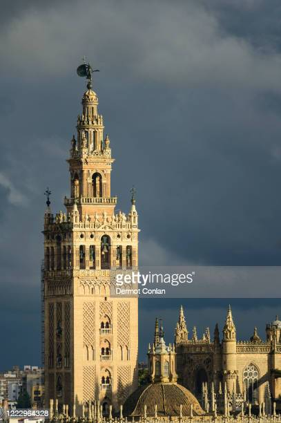 spain, seville, giralda and catherdral of seville, giralda tower with clouds - seville stock pictures, royalty-free photos & images