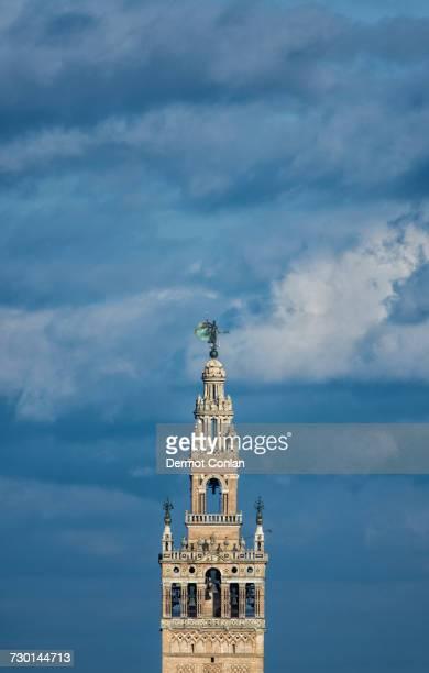 spain, seville, top of giralda tower against clouds - la giralda fotografías e imágenes de stock