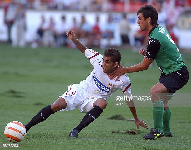 Seville's Brazilian Daniel Alves is held up by Santander's Borja Ayesa during their Spanish league football match in Seville 28 August 2005 AFP...