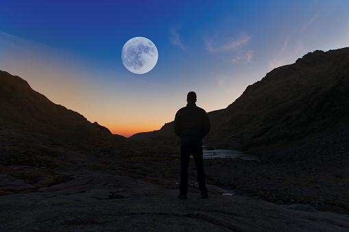 Spain, Sierra de Gredos, silhouette of man looking at the full moon - gettyimageskorea