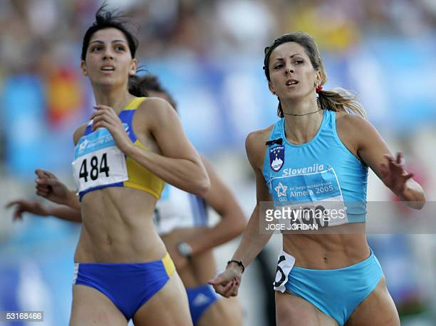 Slovenian Alenka Bikar and Cyprot Eleni Artymata cross the finish line of women's 200m final race during the XV Mediterranean Games 29 June 2005 in...