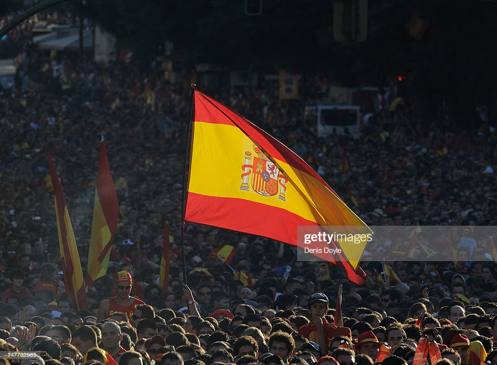 A Spain supporter flies the national flag as large crowds wait for the arrival of the Spain team parading the UEFA EURO 2012 trophy on a double-decker bus in Cibeles Square on July 2, 2012 in Madrid, Spain. Spain beat Italy 4-0 in the UEFA EURO 2012 final match in Kiev, Ukraine, on July 1, 2012.