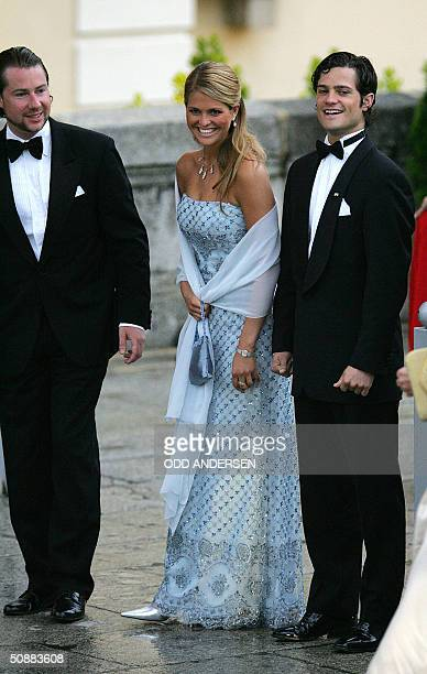 Swedish Princess Madeleine laughs with her brother Carl Philip and an unidentified person as they arrive to attend an official diner at the Pardo...
