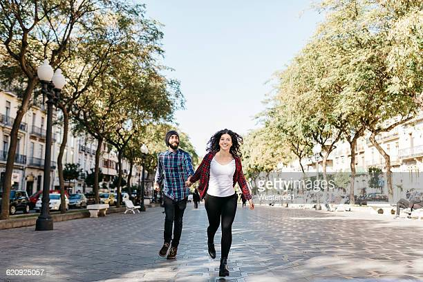 spain, tarragona, happy young couple running in the city - pedestrian stock pictures, royalty-free photos & images