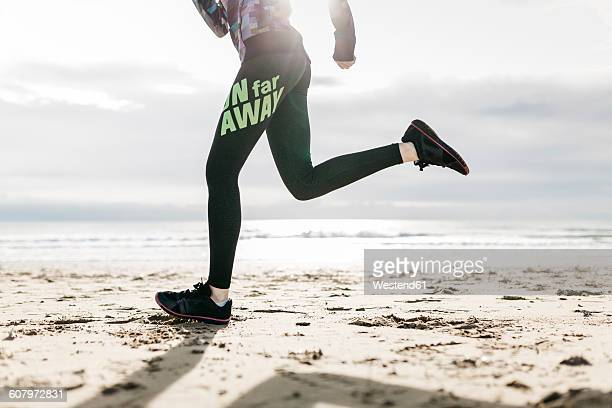 Spain, Tarragona, Legs and sneakers running in the sand of a beach