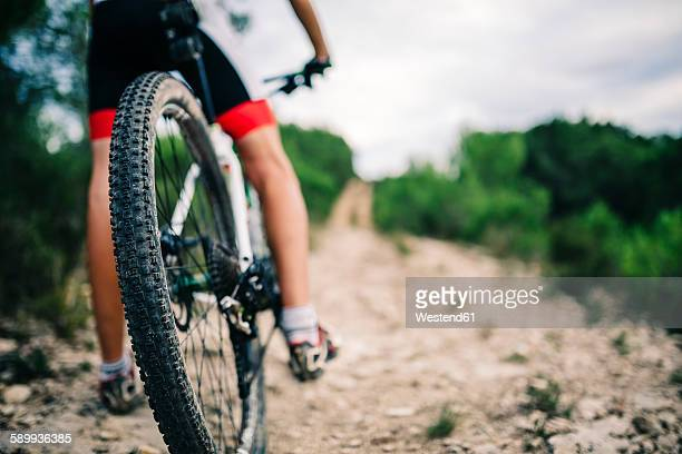 Spain, Tarragona, Mountain biker in extreme terrain, low section, rear view