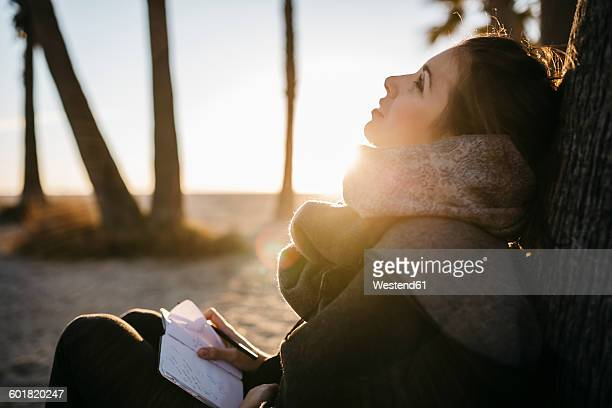 Spain, Tarragona, pensive young woman with notebook sitting on the beach at twilight