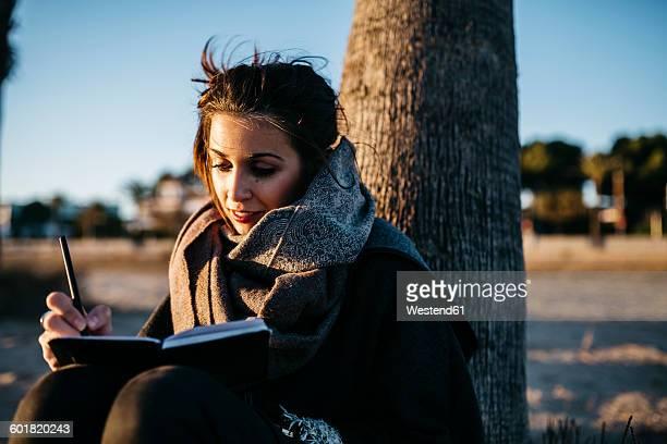 Spain, Tarragona, portrait of young woman using notebook