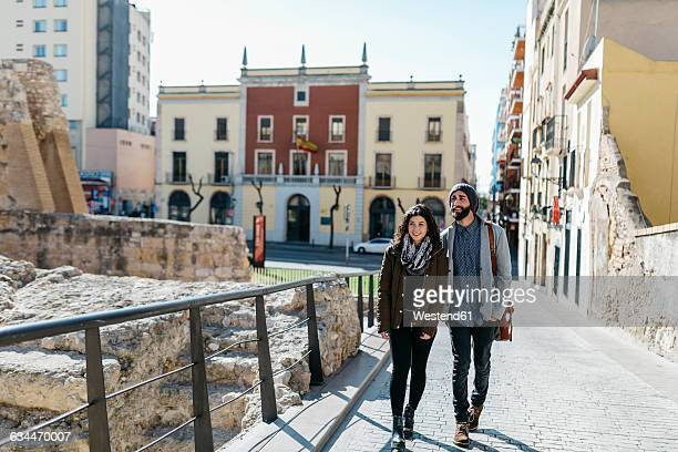 Spain, Tarragona, Young couple talking as they walk around the city