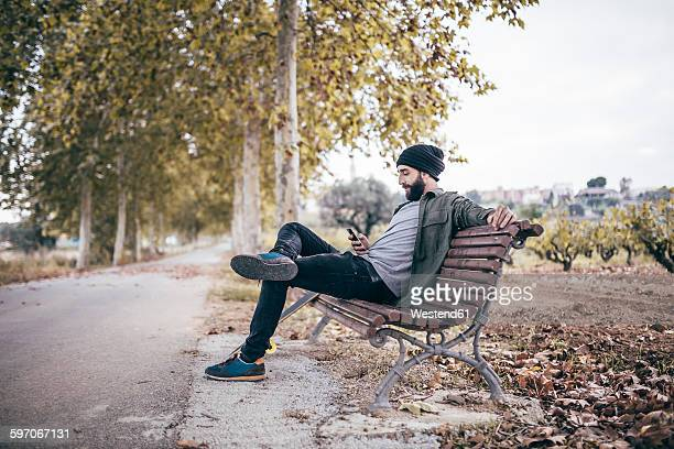Spain, Tarragona, young man sitting on a bench at autumnal country road looking at his smartphone