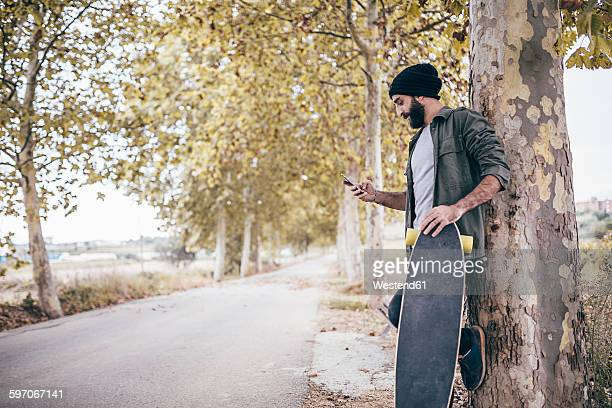 Spain, Tarragona, young man with longboard leaning against tree trunk looking at his smartphone