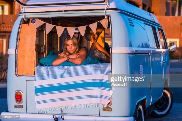 Spain, Tenerife, blond girl lying in van