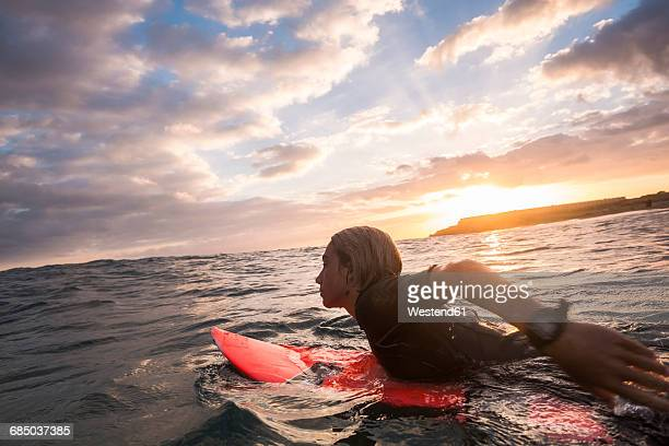 Spain, Tenerife, boy surfing in the sea at sunset