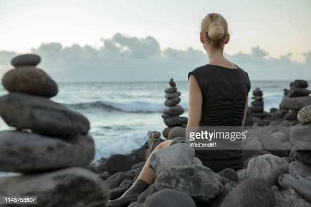 spain, tenerife, costa adeje, woman sitting between cairns at the coast - 石塚 ストックフォトと画像