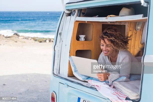 Spain, Tenerife, happy woman using laptop in van
