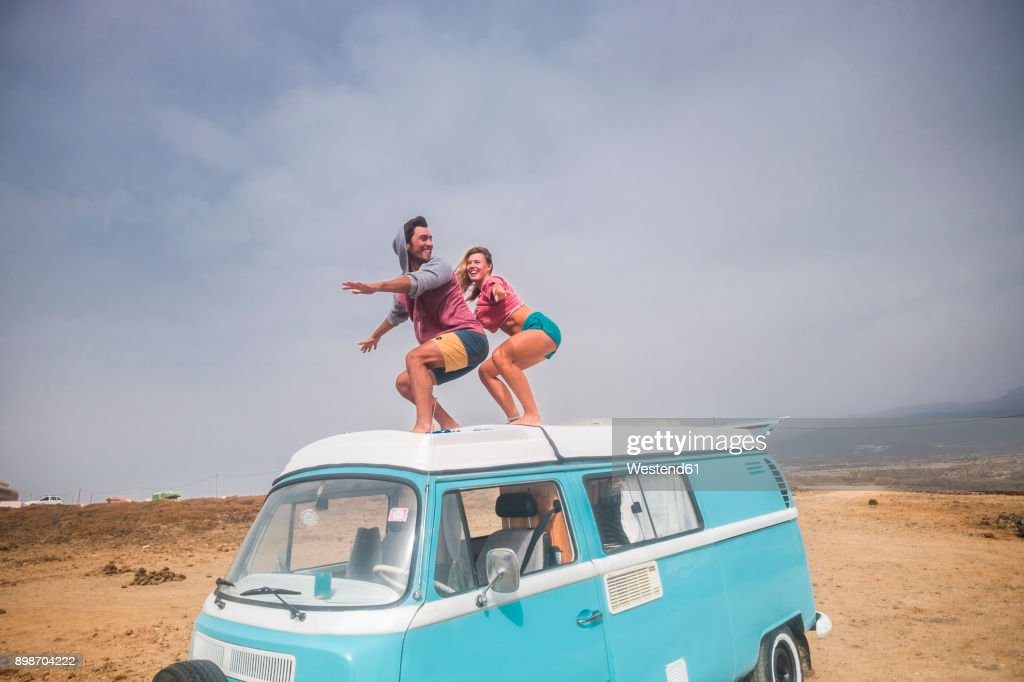Spain, Tenerife, laughing young couple standing on car roof enjoying freedom : Foto de stock