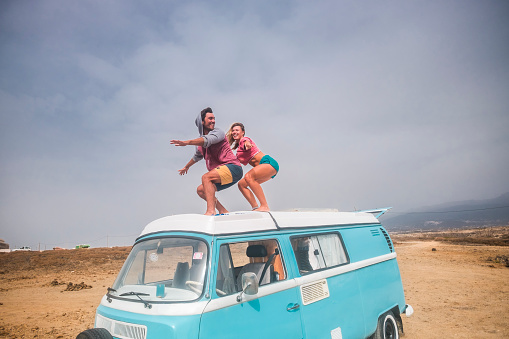 Spain, Tenerife, laughing young couple standing on car roof enjoying freedom - gettyimageskorea