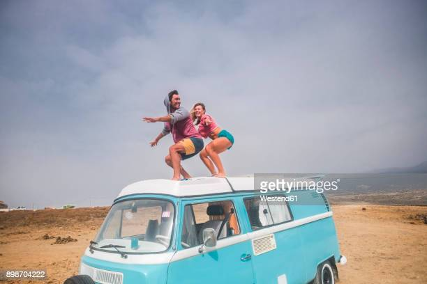 spain, tenerife, laughing young couple standing on car roof enjoying freedom - spaß stock-fotos und bilder