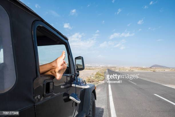 Spain, Tenerife, legs of woman leaning out of car window