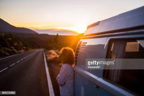 spain, tenerife, pensive woman at sunset leaning against van parked at roadside - straßenrand stock-fotos und bilder