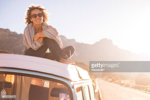 Spain, Tenerife, portrait of happy woman sitting on car roof of van at twilight