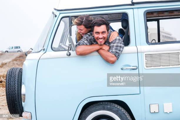 spain, tenerife, portrait of laughing man and his girlfriend leaning out of car window of camper - leaning stock pictures, royalty-free photos & images