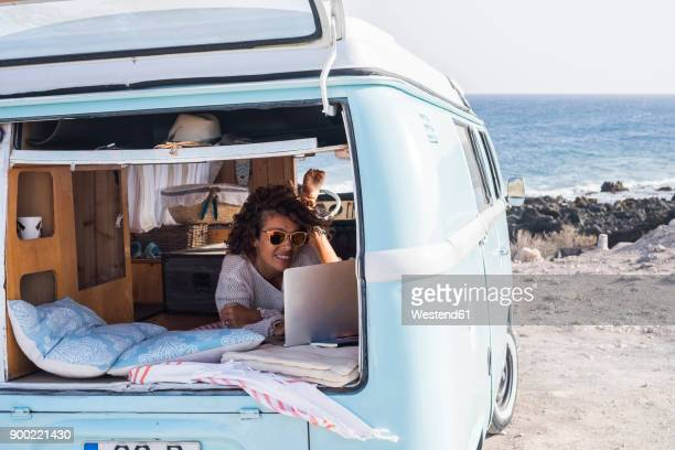 spain, tenerife, smiling woman looking at laptop in van - mini van stock photos and pictures