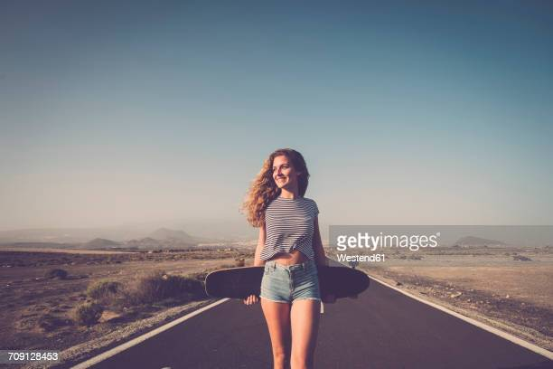 Spain, Tenerife, smiling woman with longboard standing on empty country road