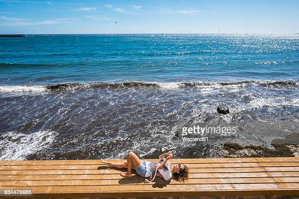 Spain, Tenerife, woman lying on a bench in front of the sea taking a selfie with her smartphone