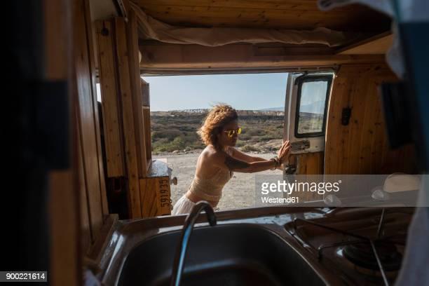 Spain, Tenerife, woman opening sliding door of parked van