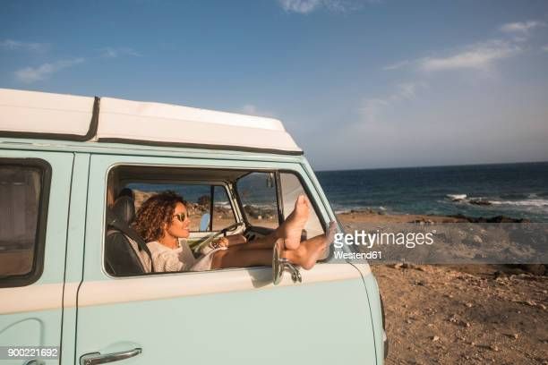 spain, tenerife, woman sitting with feet up in van parked at seaside - minivan stock photos and pictures