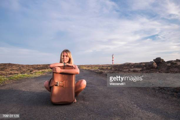 Spain, Tenerife, young blond woman sitting on empty street with suitcase
