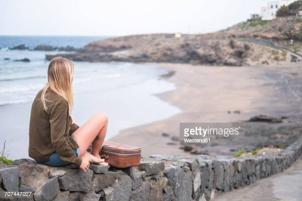 Spain, Tenerife, young blond woman sitting on wall near the beach