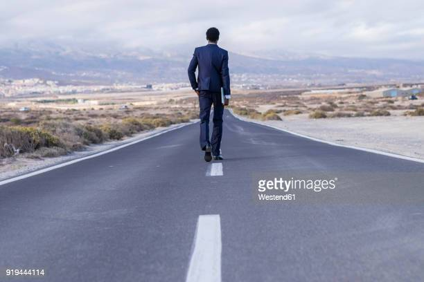 Spain, Tenerife, young businessman with laptop walking on road