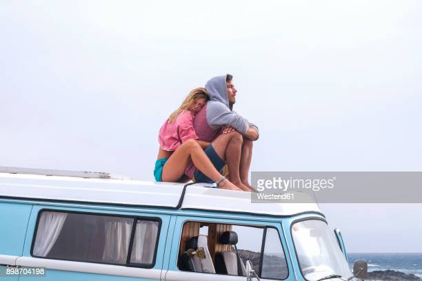 Spain, Tenerife, young couple in love relaxing on car roof of van