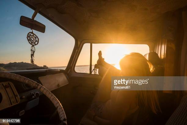 spain, tenerife, young woman lying in a van at sunset - camping stock-fotos und bilder