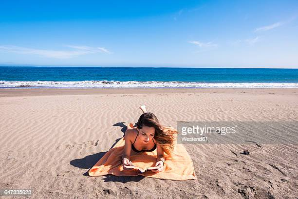 Spain, Tenerife, young woman reading book on the beach