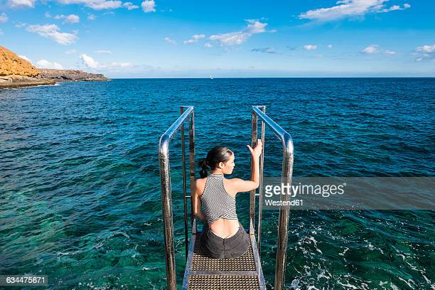 Spain, Tenerife, young woman sitting on a platform in front of the sea