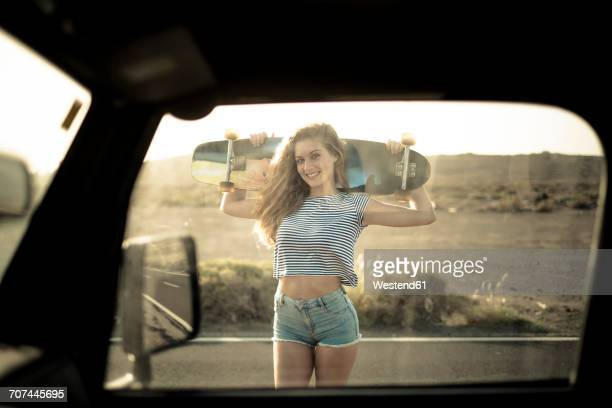 Spain, Tenerife, young woman with skateboard seen through car window