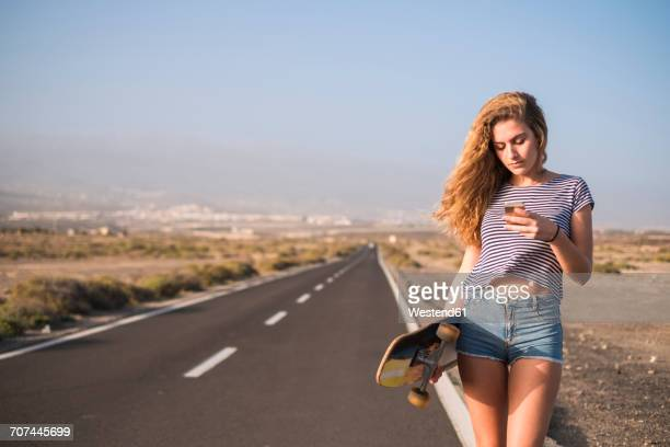 Spain, Tenerife, young woman with skateboard standing on empty country road looking at smartphone