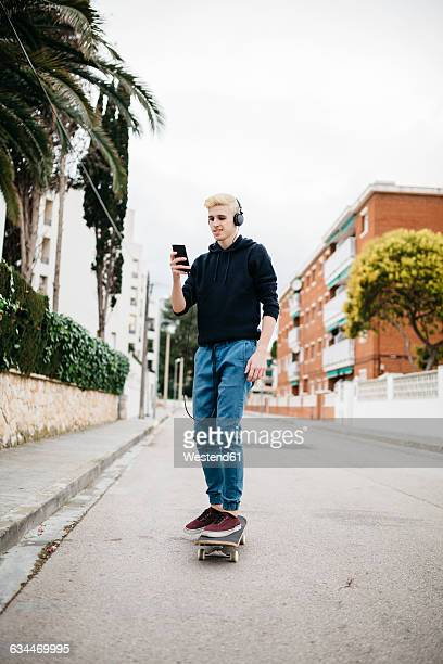Spain, Torredembarra, young man with headphones standing on skateboard looking at his smartphone